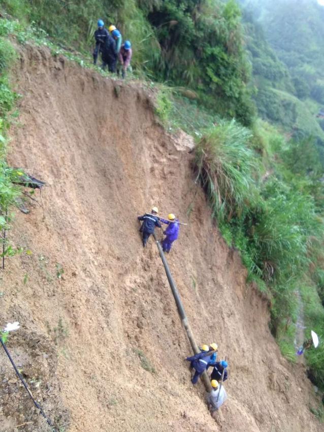 大雨倾盆,工人抬1吨电杆爬悬崖送电